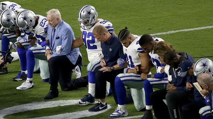 The Dallas Cowboys and owner Jerry Jones take a knee before the National Anthem during their week three contest.  via variety.com