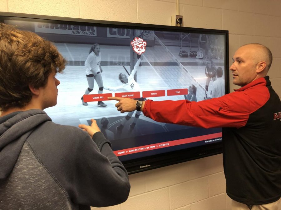 MCHS+Athletic+Director+Joe+Bronkella+shows+a+student+the+features+of+the+new+digital+board+for+MCHS+Hall+of+Fame.