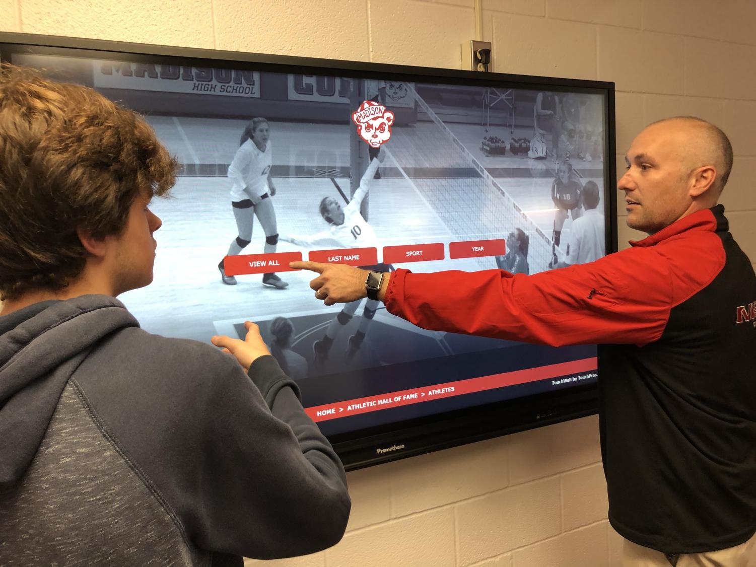MCHS Athletic Director Joe Bronkella shows a student the features of the new digital board for MCHS Hall of Fame.