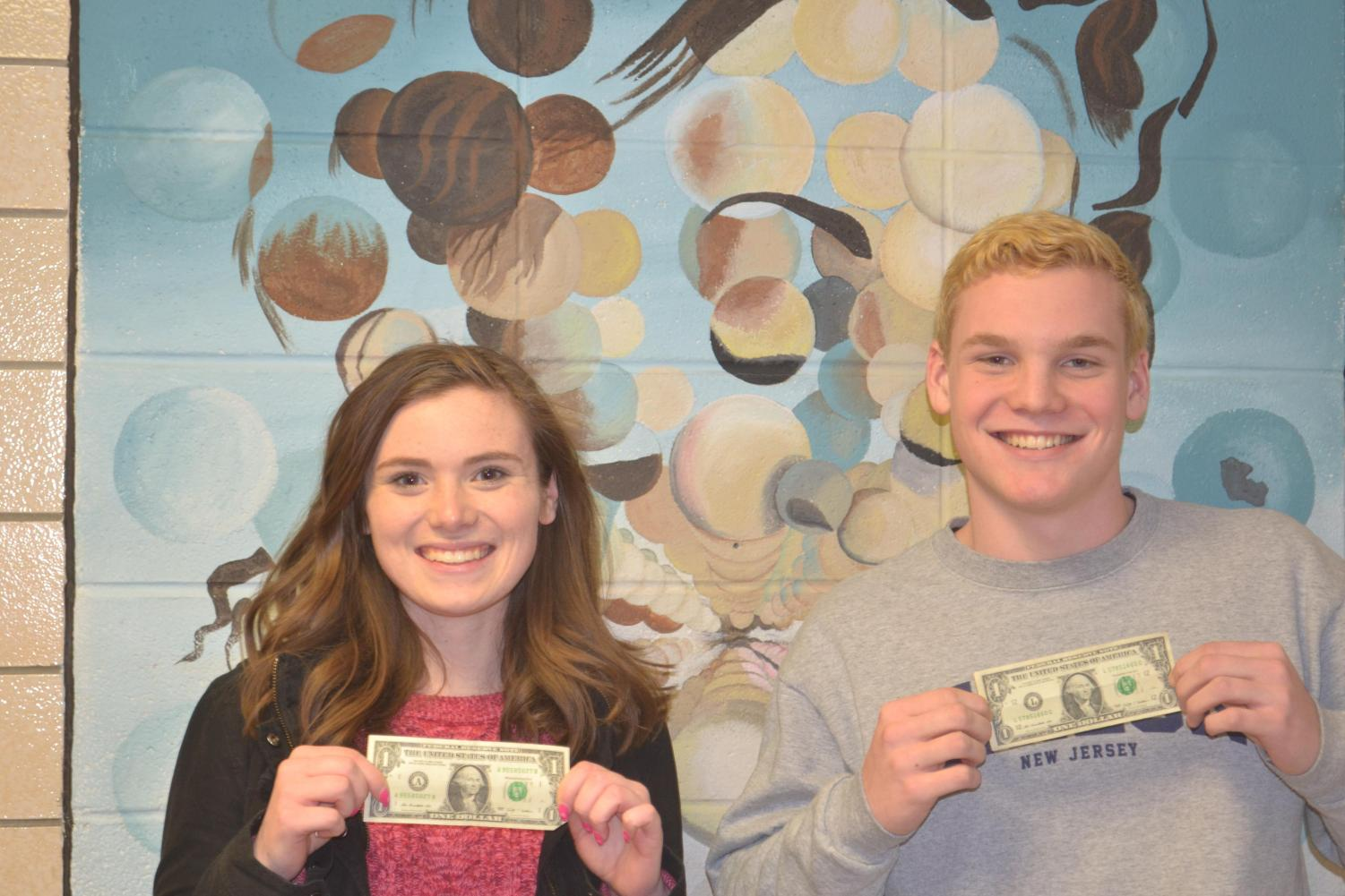 Seniors Hannah Huff and Eoin McMahon display dollar bills after winning the most likely to be a millionaire superlative.