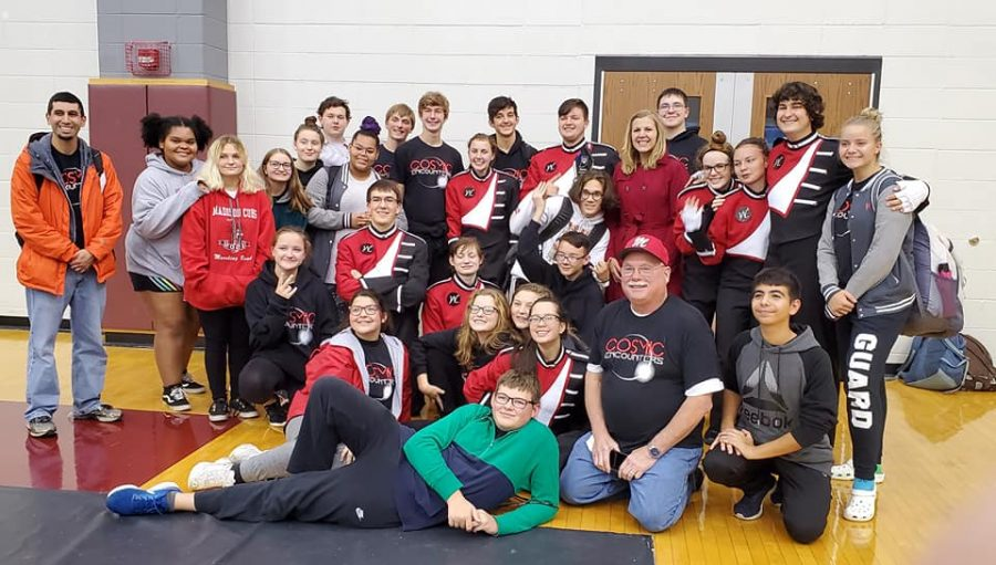 The+MCHS+Marching+Band+huddles+together+for+a+photo+opportunity+at+the+state+finals.