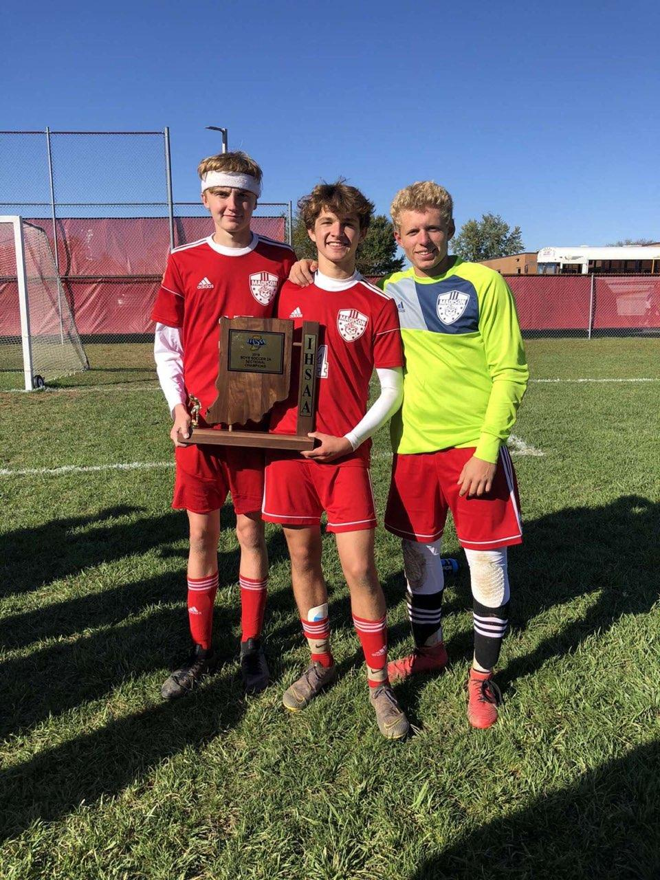 Juniors Smith, Zach Forner, and Will Heitz pose with the sectional championship trophy,
