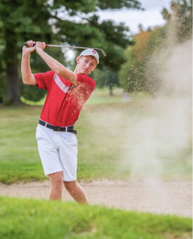 Senior Cub basketball player and golfer, Luke Ommen, blasts a bunker shot for the camera.
