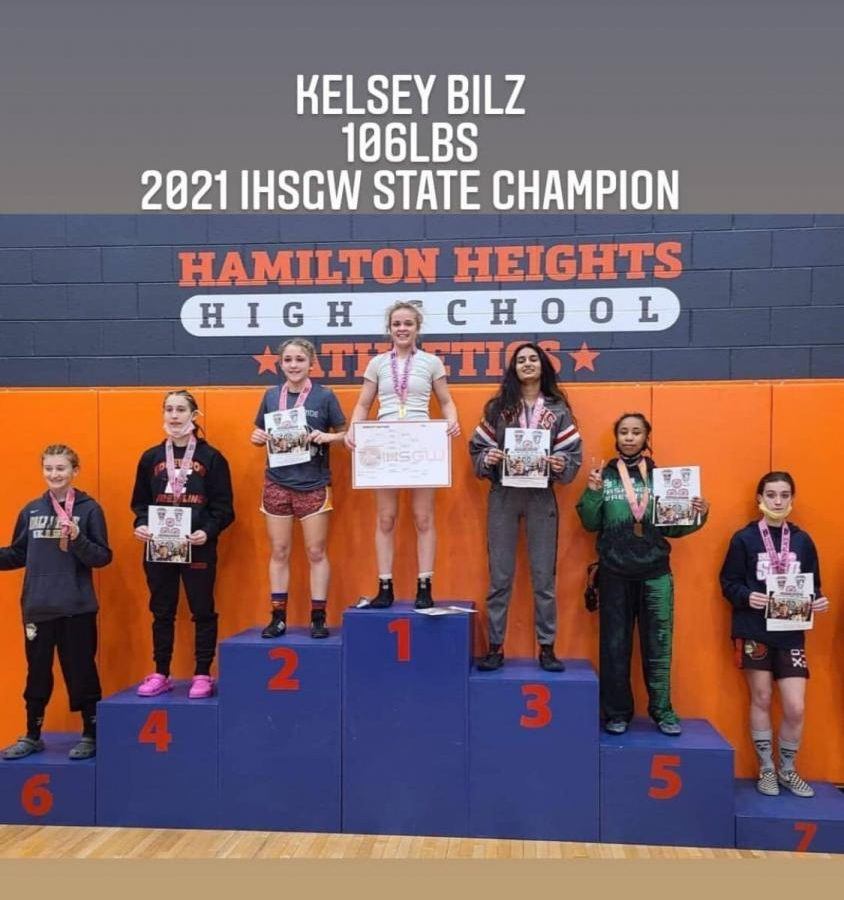 Kelsey Bilz stands atop the podium after winning the female wrestling state championship.